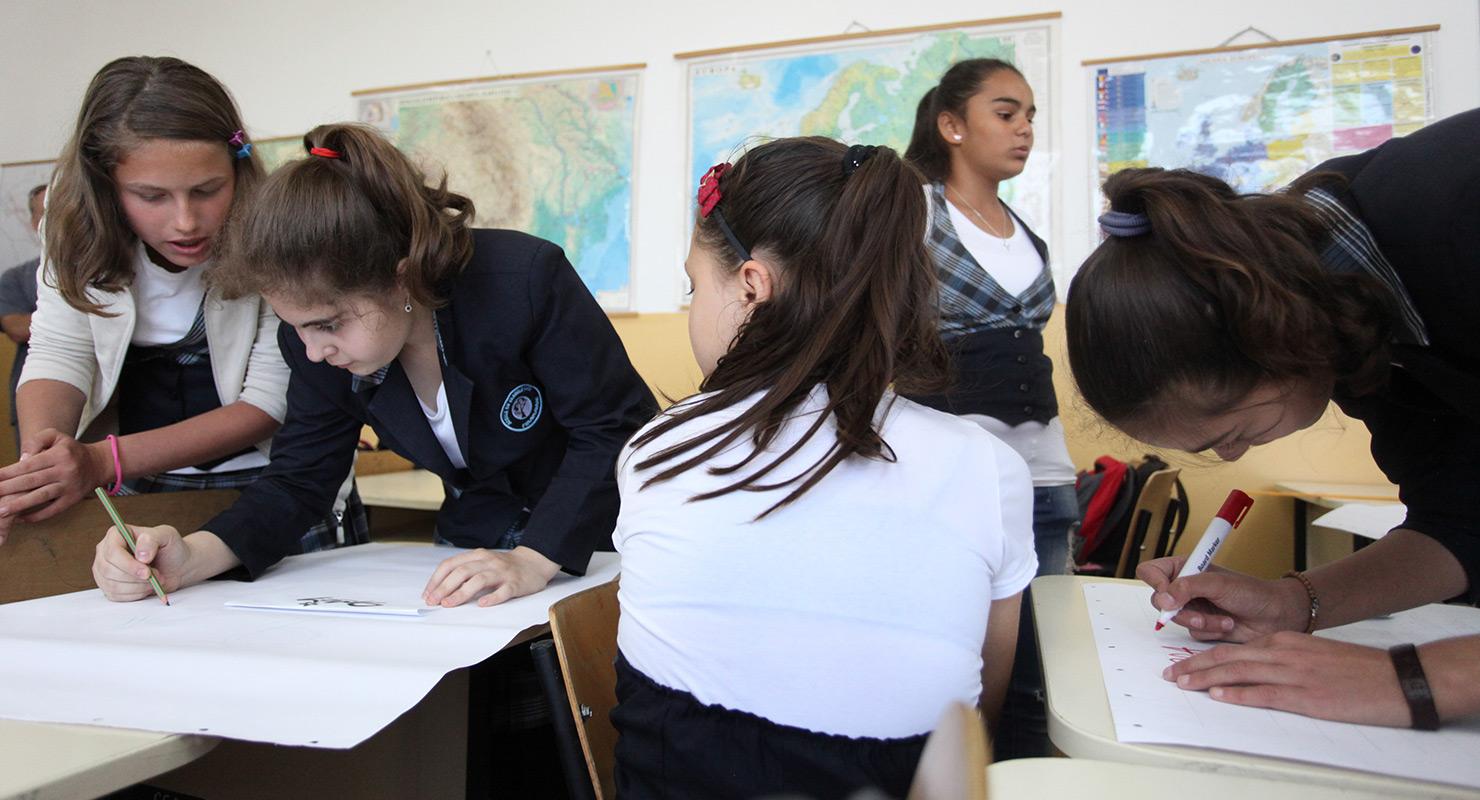 Együtt dolgozó diákok a romániai Frumusani faluban lévő Scoala Frumusani iskolában 2013 májusában a világbank elknökének látogatása előtt. Forrás: Világbank/Dominic Chavez CC BY-NC-ND https://www.flickr.com/photos/worldbank/8720779572